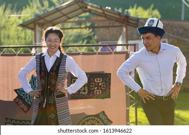 Bishkek province, Kyrgyzstan - April 28, 2018: a couple in traditional dresses dancing local music in the kyrgyz countryside