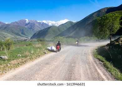 Bishkek province, Kyrgyzstan - April 28, 2018: men on motorbikes on a dusty gravel road in the kyrgyz countryside