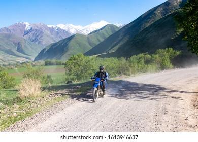 Bishkek province, Kyrgyzstan - April 28, 2018: man on motorbike on a dusty gravel road in the kyrgyz countryside