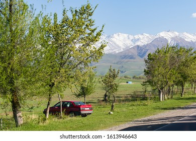 Bishkek province, Kyrgyzstan - April 28, 2018: a red car in the kyrgyz countryside with on the background mountains covered with snow
