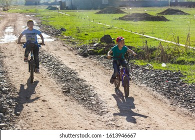 Bishkek province, Kyrgyzstan - April 28, 2018: two children riding bicycles in the kyrgyz countryside