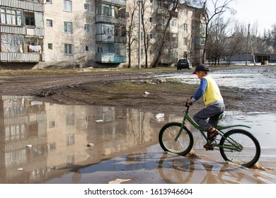 Bishkek province, Kyrgyzstan - February 24, 2017: a chilld riding a bicycle with hisimage reflected on a puddle
