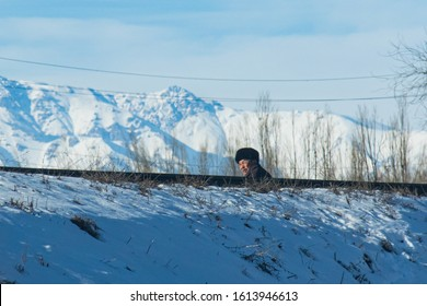 Bishkek province, Kyrgyzstan - February 24, 2017: a man and a railway road in the snowy kyrgyz coutryside