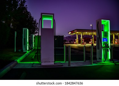 Bishop, California / USA - October 27 2020: Green lights of electric vehicle charging stations at night and gas station