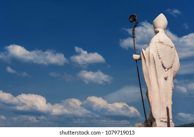 Bishop with crosier, blue sky and clouds. White marble statue on Lucca old walls, erected in the 17th century (with copy space)