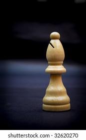 Bishop, wooden chess piece isolated on dark background.