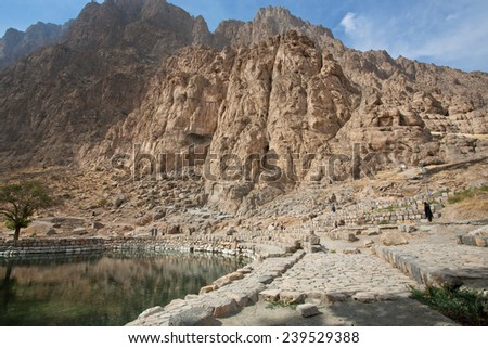 BISOTUN, IRAN - OCT 12: Mountains and clean water lake in beautiful persian valley with historical rocky reliefs on October 12, 2014. Bisotun of Kermanshah Province is the UNESCO World Heritage site
