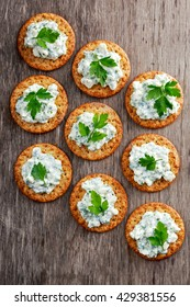 Bisquit cracker appetizers with cottage chees and parsley topping