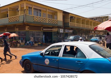 Bissau, Guinea Bissau - January 30, 2018: Street scene in the city of Bissau with a taxi and people crossing a dirt road, in Guinea Bissau, West Africa