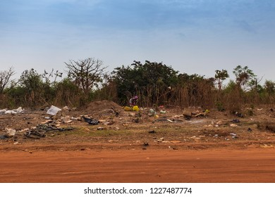 Bissau, Republic of Guinea-Bissau - February 5, 2018: Woman collecting garbage in a landfill in the outskirts of the city of Bissau, in Guinea-Bissau, West Africa
