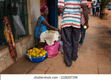 Bissau, Republic of Guinea-Bissau - February 5, 2018: Street scene in the city of Bissau with a woman selling oranges, in Guinea-Bissau, West Africa