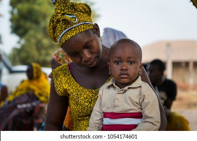 Bissau, Republic of Guinea-Bissau - January 29, 2018: Portrait of a young mother and her son, at the Bissaque neighborhood in the city of Bissau, Guinea Bissau.