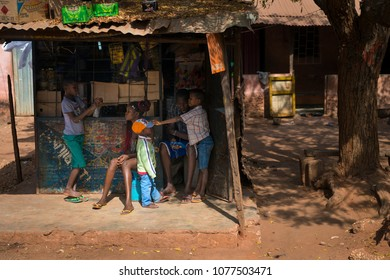 Bissau, Republic of Guinea-Bissau - January 29, 2018: Young family in front of their small store in a slum of the city of Bissau, Guinea Bissau.