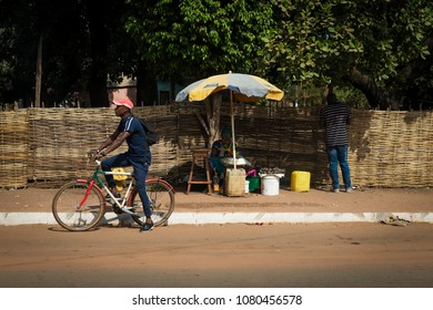 Bissau, Republic of Guinea-Bissau - January 29, 2018: Street scene in the city of Bissau with a woman selling fruit and two man, in Guinea-Bissau, West Africa