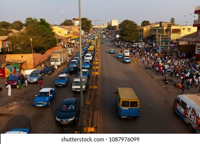 Bissau, Republic of Guinea-Bissau - January 30, 2018: Street scene in the city of Bissau during rush hour with cars in an avenue and people at the Bandim Market, in Guinea-Bissau, West Africa