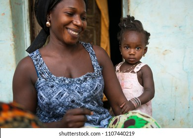 Bissau, Republic of Guinea-Bissau - January 31, 2018: Portrait of a mother and her baby daughter at the Cupelon de Cima neighborhood in the city of Bissau, Guinea Bissau