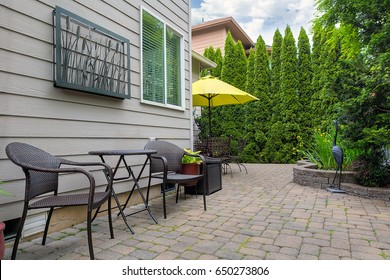 Bistro chairs and table on stone paver bricks patio in garden backyard with pond spring season