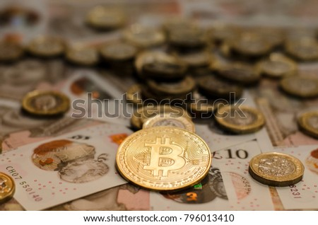 A bit coin on with UK pound sterling background