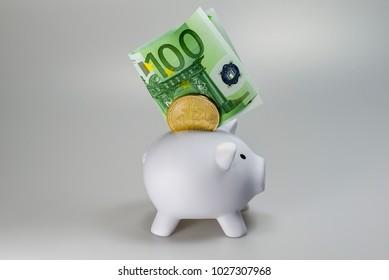 A bitcoin and a 100 euro bill in a white piggy bank
