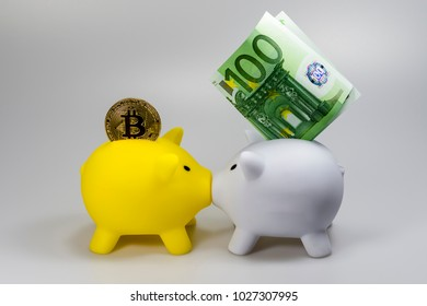 A bitcoin, a 100 euro bill and a yellow and a white piggy bank in front of a white background