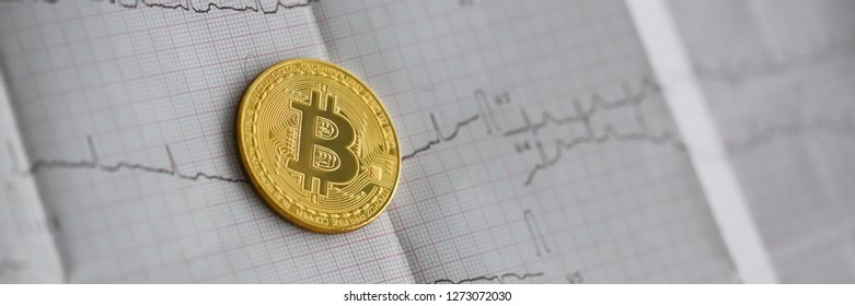 Bitcoin is alive. The gold coin lies on a paper cardiogram sheet of people heartbeat