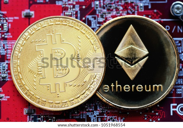 Bitcoin, BTC, Bit Coin. Crypto currency Ethereum, ETH, Crypto Coin. Macro shot of Bitcoin and Ethereum golden coins on a red computer board background. Blockchain technology, mining concept
