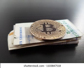 Bitcoin BTC coin on a stack of currency from Denmark, danske kroner. The Bitcoin is seen from the side below, with a dark wooden theme background.