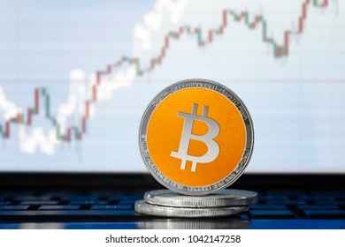 BITCOIN (BTC) cryptocurrency; physical concept bitcoin coin on the background of the chart