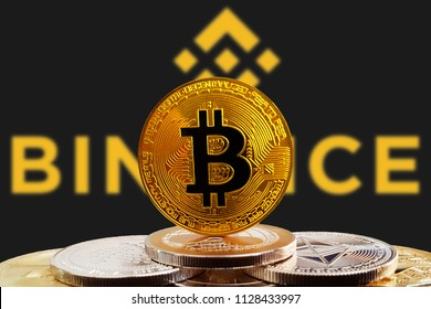 Bitcoin BTC on stack of cryptocurrencies with Binance coin logo in background. The cryptocurrency coin is golden and in focus. Copenhagen / Denmark - 07 06 2018
