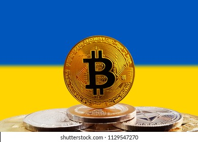 Bitcoin BTC on stack of cryptocurrencies with Ukraine flag in background. The cryptocurrency coin is golden and in focus