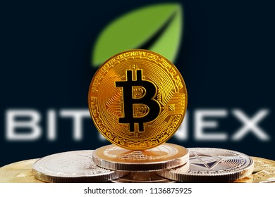 Bitcoin BTC on stack of cryptocurrencies with Bitfinex exchange logo in background. The cryptocurrency coin is golden and in focus. Copenhagen / Denmark - 07 18 2018