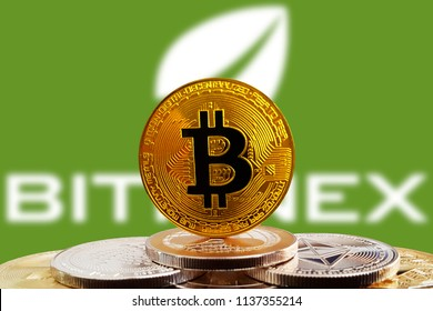 Bitcoin BTC on stack of cryptocurrencies with green Bitfinex exchange logo in background. The cryptocurrency coin is golden and in focus. Copenhagen / Denmark - 07 19 2018