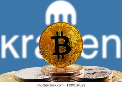 Bitcoin BTC on stack of cryptocurrencies with Kraken exchange logo blue in background. The cryptocurrency coin is golden and in focus. Copenhagen / Denmark - 07 21 2018