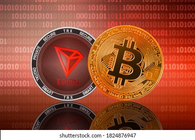Bitcoin BTC and Tron TRX coins on the binary code background; bitcoin and tron cryptocurrency
