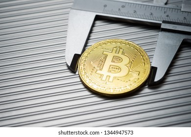 Bitcoin and caliper on a metal table.