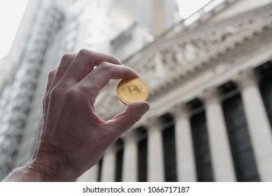 Bitcoin coin being held up outside the New York City Stock exchange building.