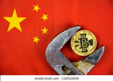 BITCOIN coin being squeezed in vice on China flag background; concept of cryptocurrency bitcoin (btc) under pressure. Prohibition of cryptocurrencies, regulations, restrictions or security