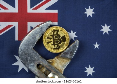 BITCOIN coin being squeezed in vice on Australia flag background; concept of cryptocurrency bitcoin (btc) under pressure. Prohibition of cryptocurrencies, regulations, restrictions or security