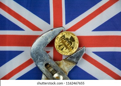 BITCOIN coin being squeezed in vice on Great Britain flag background; concept of cryptocurrency bitcoin (btc) under pressure. Prohibition of cryptocurrencies, regulations, restrictions or security