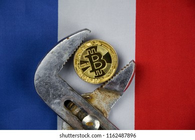 BITCOIN coin being squeezed in vice on France flag background; concept of cryptocurrency bitcoin (btc) under pressure. Prohibition of cryptocurrencies, regulations, restrictions or security