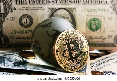 bitcoin coin and cristal globe over  one dollar banknote