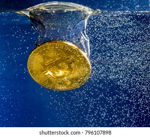 Bitcoin coin dropped into water and sinking below bubble to show the falling price of cyber currency