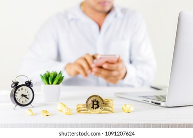 Bitcoin coin golden coin in the glass jar on wooden table,Man using smartphone for trading cryptocurrency or bitcion.Set of cryptocurrencies with a golden bitcoin as most important cryptocurrency.