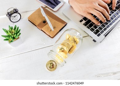 Bitcoin coin golden coin in the glass jar on wooden table ,Man using tablet for trading cryptocurrency or bitcion.Set of cryptocurrencies with a golden bitcoin