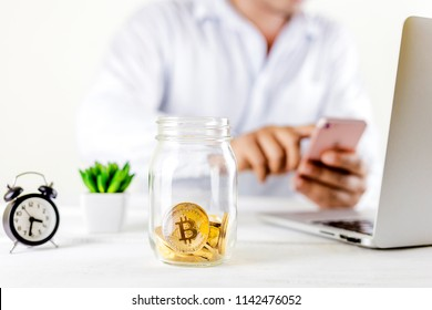 Bitcoin coin golden coin in the glass jar on wooden table ,Man using smartphone for trading cryptocurrency or bitcion.Set of cryptocurrencies with a golden bitcoin