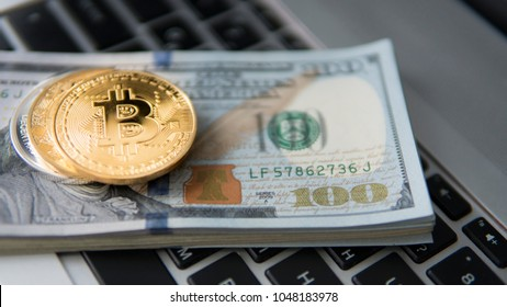 Bitcoin coin with laptop and us dollars. Bitcoin golden coins on a dollar banknotes office background white laptop mobile. Digital crypto currency. Metal coins of bitcoin. Bussiness, commercial.