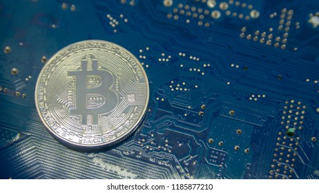 a bitcoin coin on blue electronic circuit