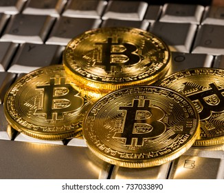 Bitcoin coin on a silver keyboard on a computer to illustrate blockchain and cyber currency