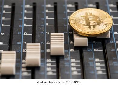 Bitcoin coin on the sound mixer console. Concept idea