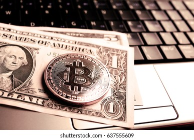bitcoin coin and one dollar banknote on laptop keyboard